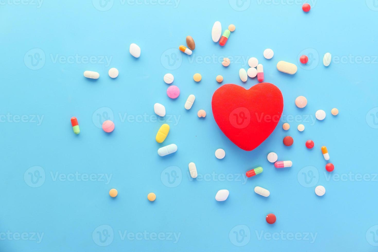 formato de coração com comprimidos em fundo azul foto