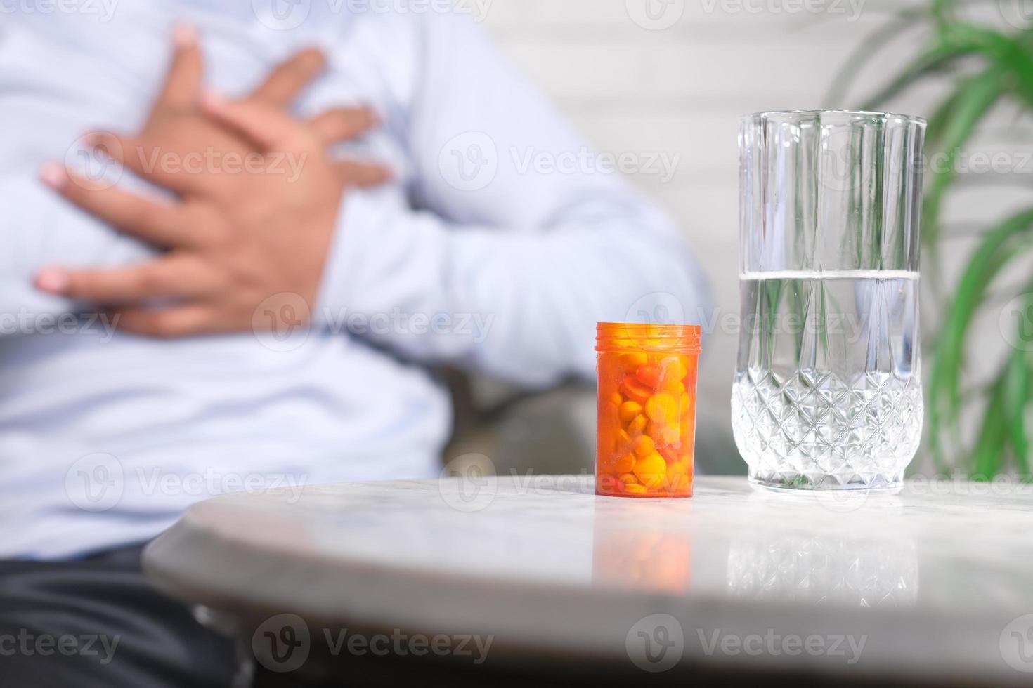 comprimidos e um copo de água foto