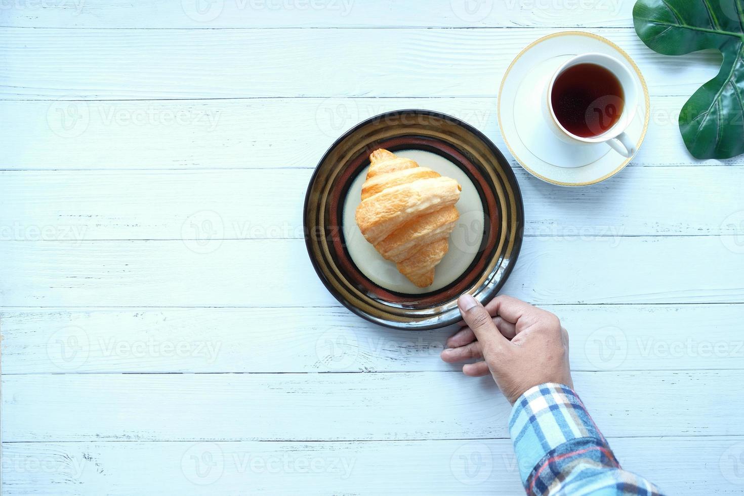 croissant e café na mesa foto
