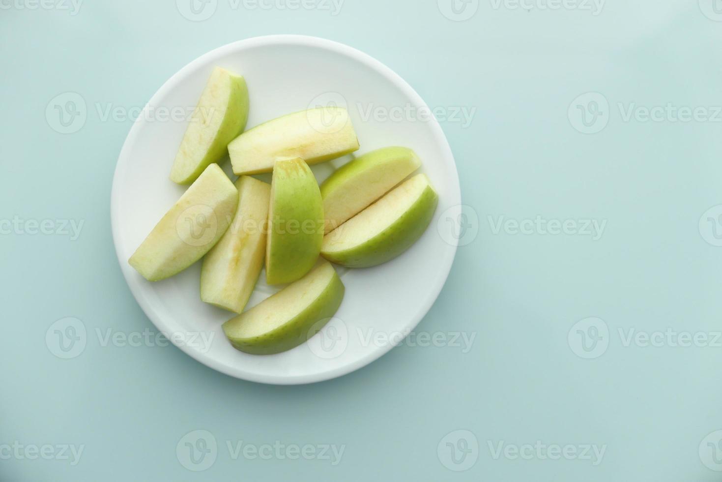 fatias de maçã verde sobre fundo azul foto