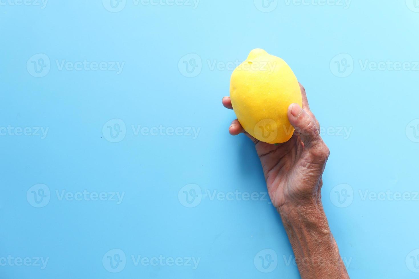 velha segurando limão sobre fundo azul foto