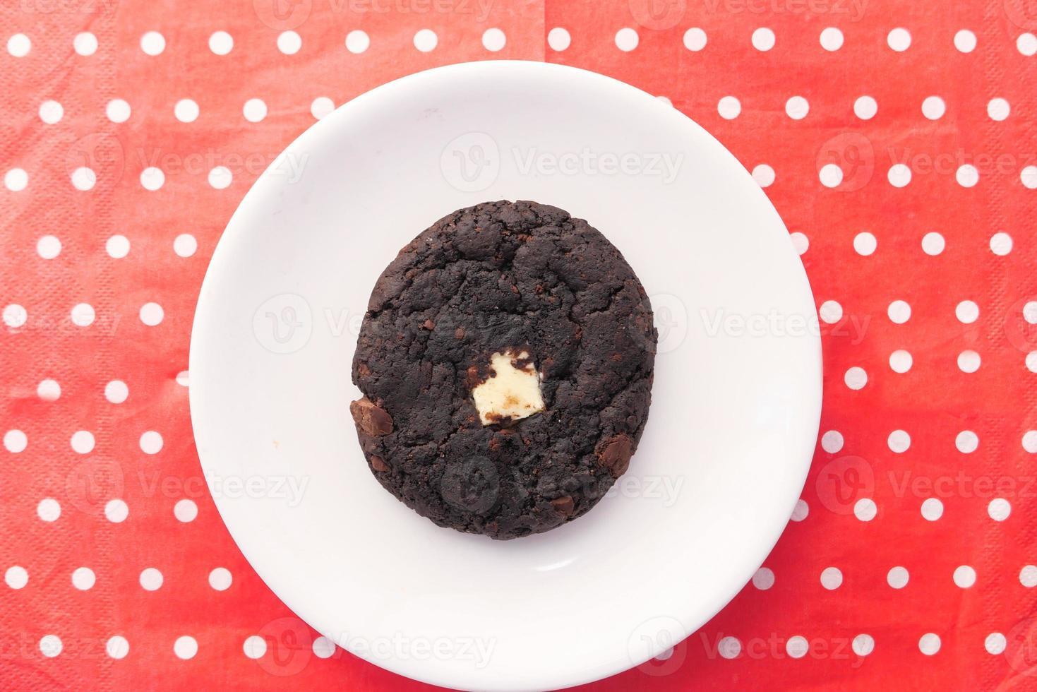 biscoito de chocolate em fundo de bolinhas vermelhas foto
