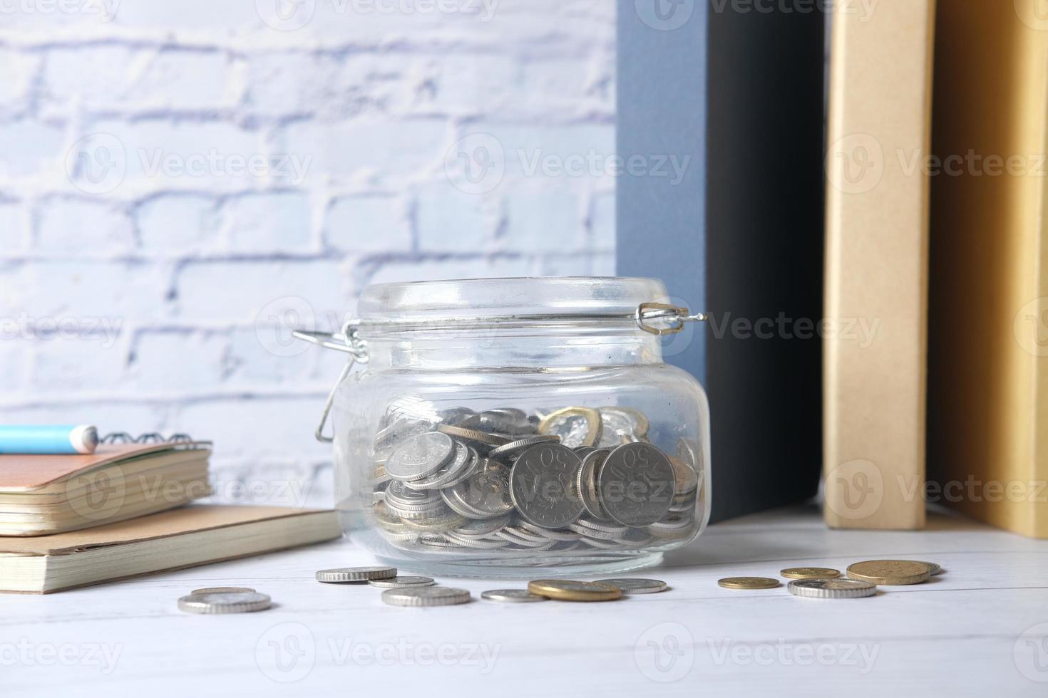 economizando moedas em uma jarra foto