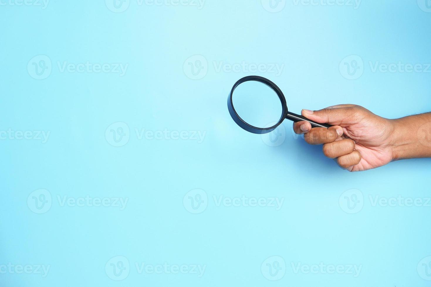 mão segurando uma lupa sobre um fundo azul foto