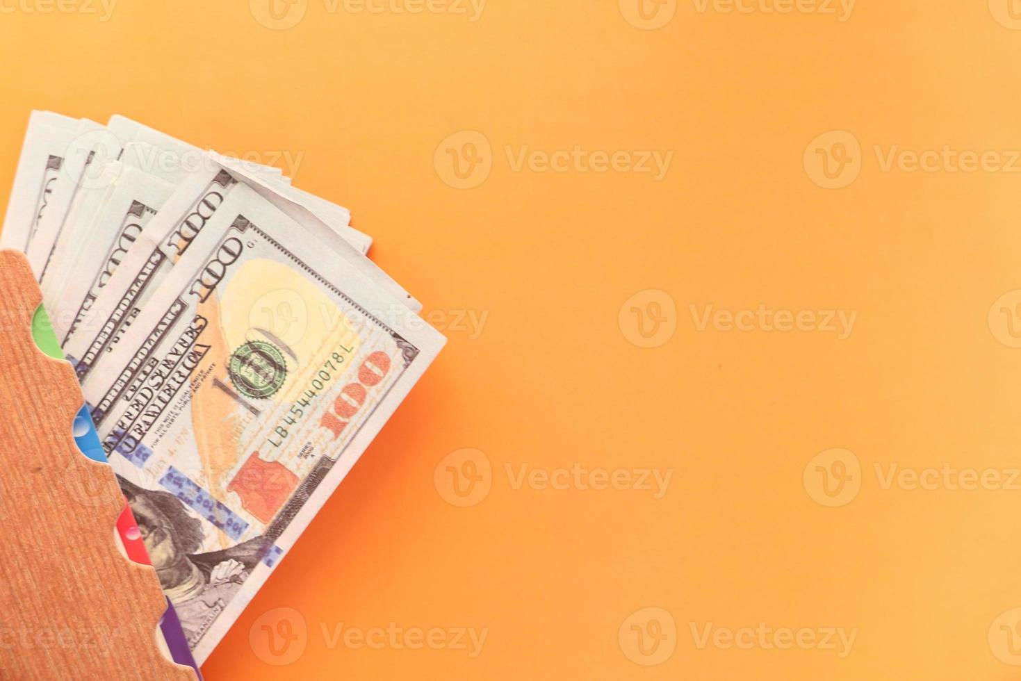 close-up de 100 dólares em dinheiro em fundo laranja foto
