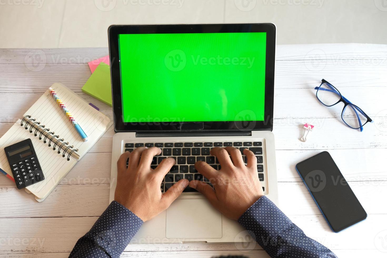 homem usando um laptop em um escritório doméstico foto