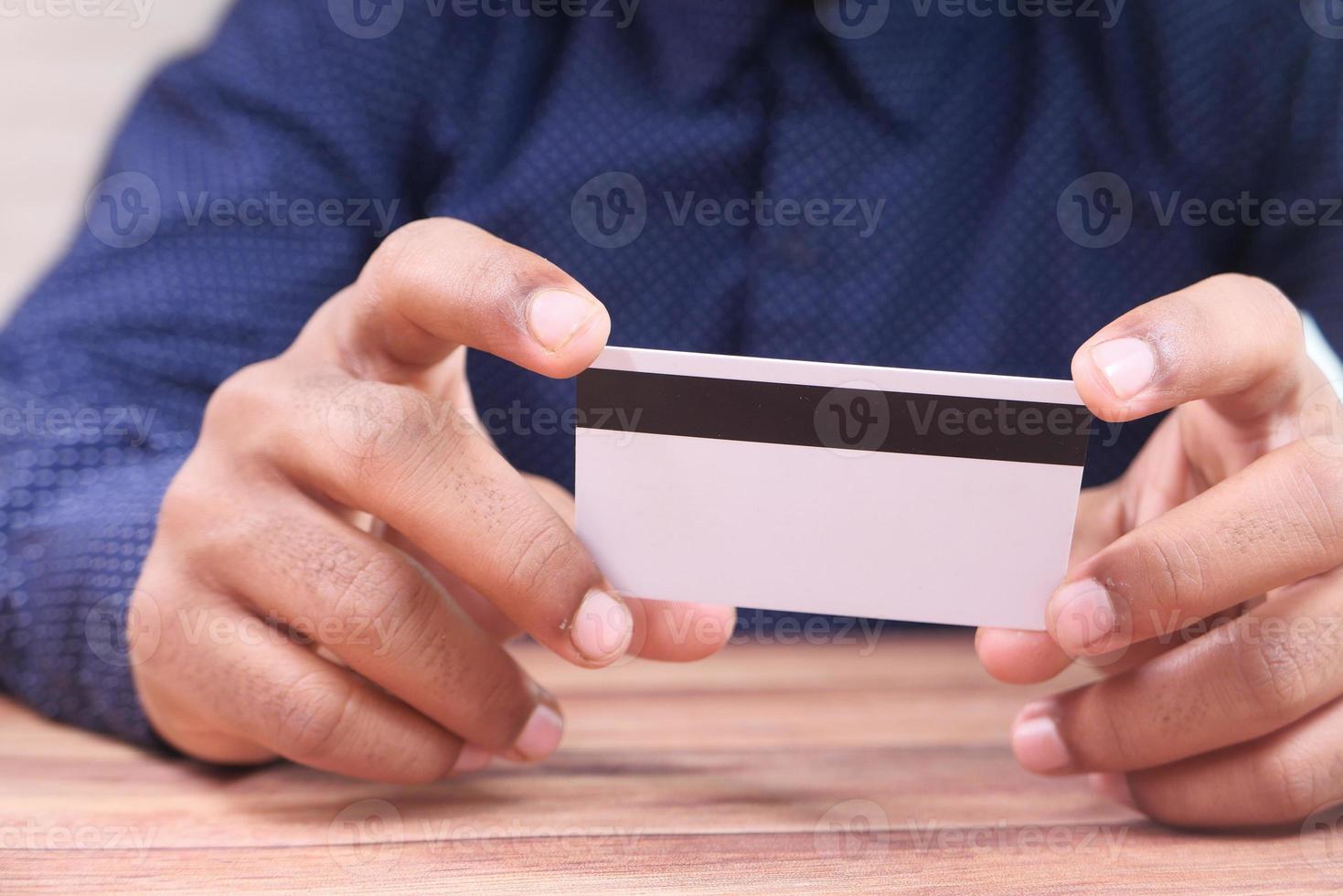 homem segurando cartão de crédito foto