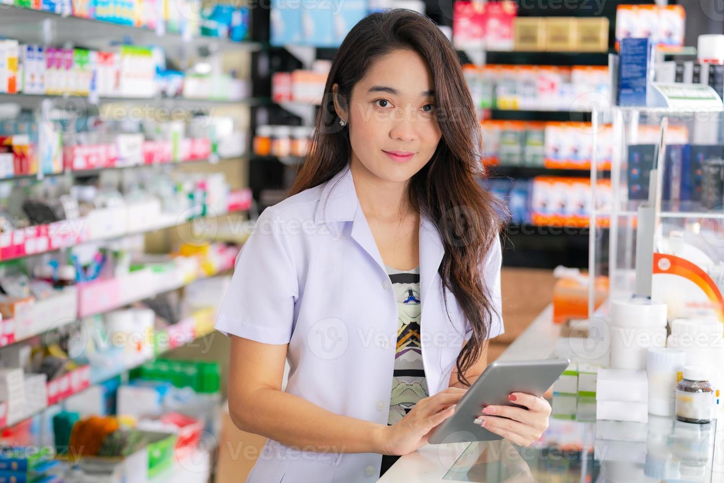 farmacêutica asiática usa tablet digital na farmácia foto