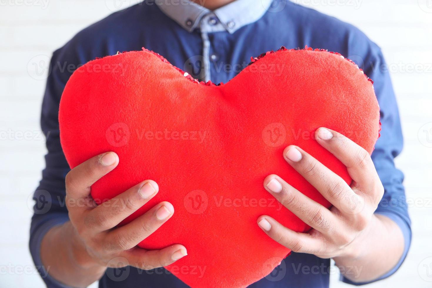 mão segurando o símbolo do coração vermelho sobre fundo branco foto