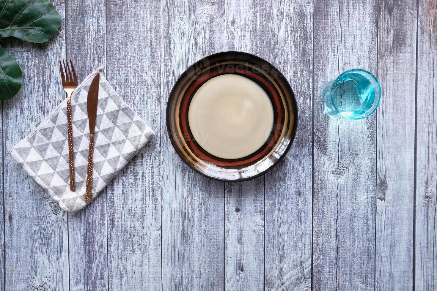 prato vazio com uma faca e um garfo no fundo de madeira foto