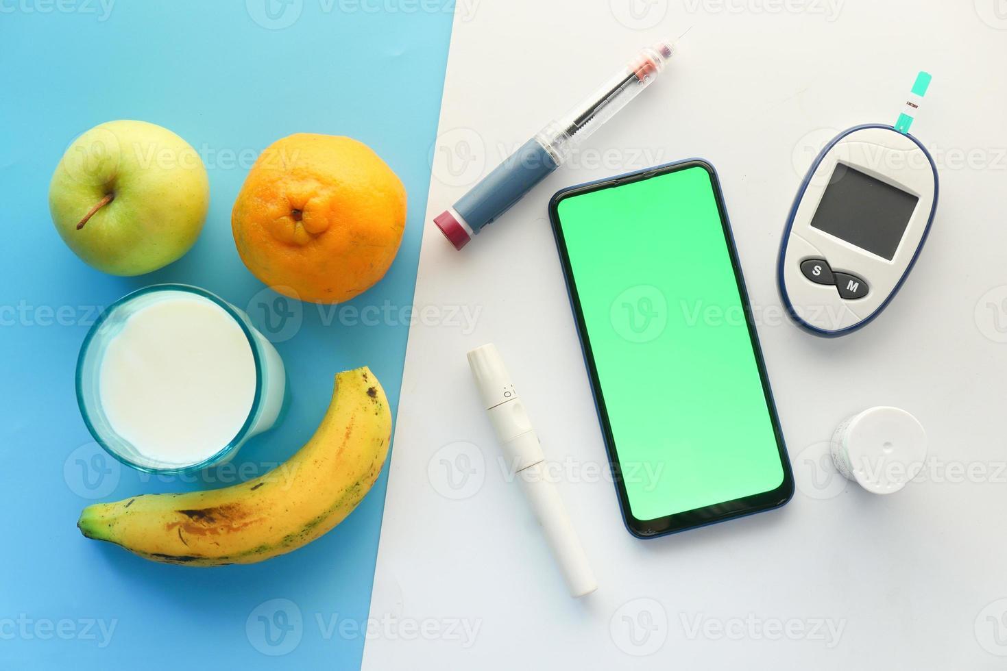 frutas, telefone inteligente e insulina em fundo branco e azul foto