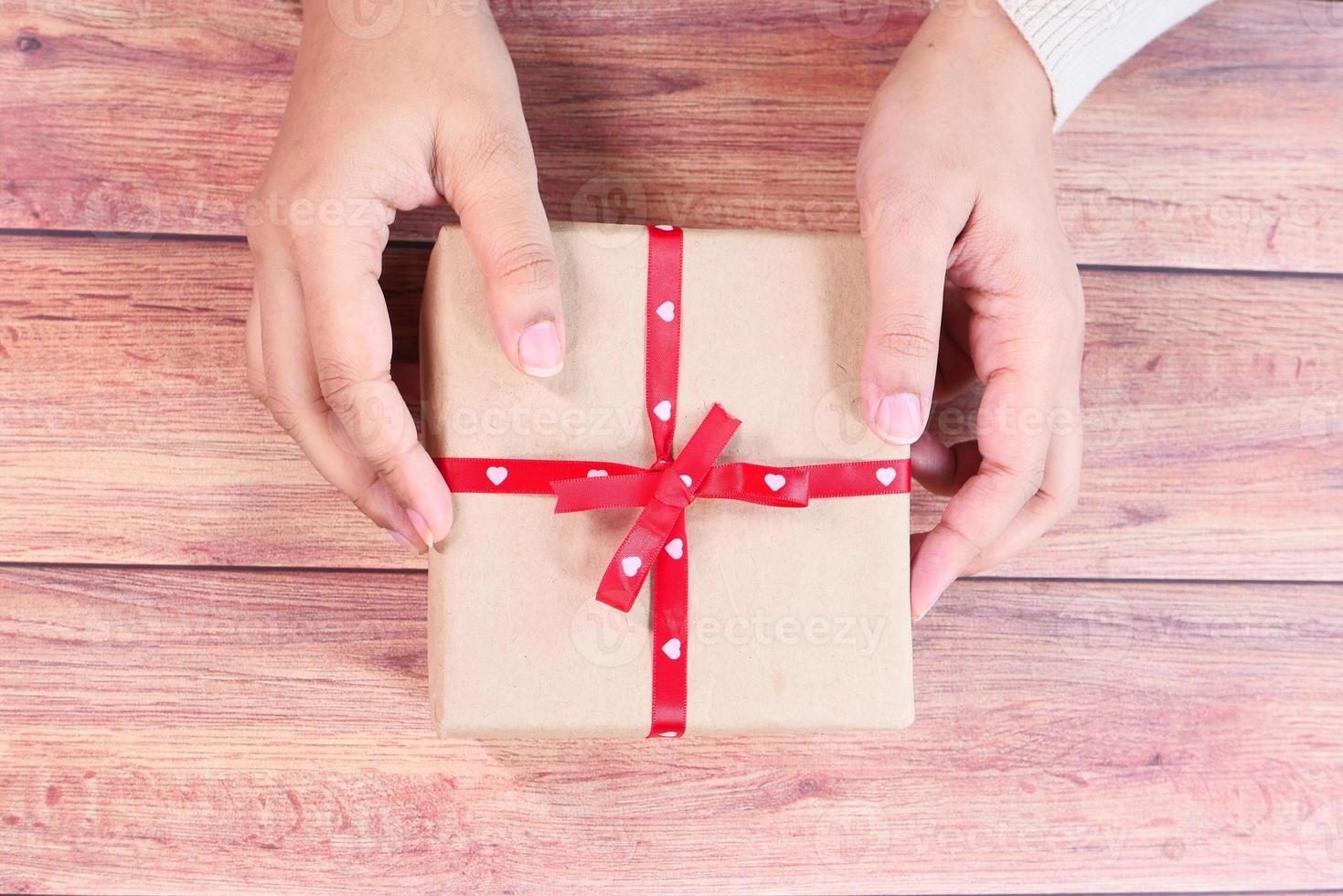 segurando uma caixa de presente na mesa de madeira foto