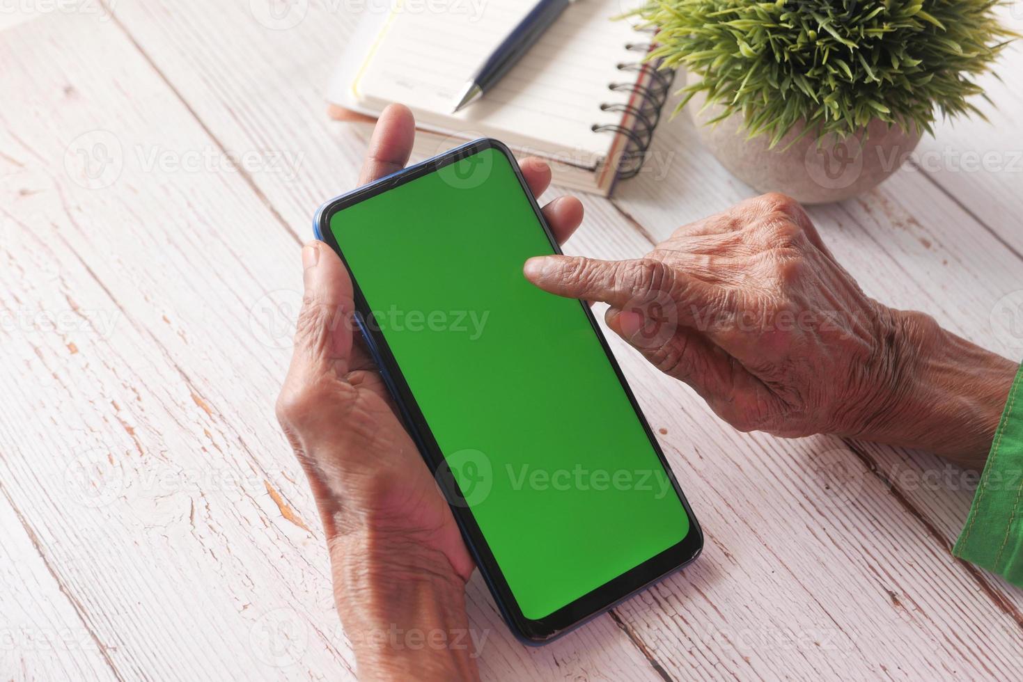 pessoa usando telefone inteligente com tela verde foto