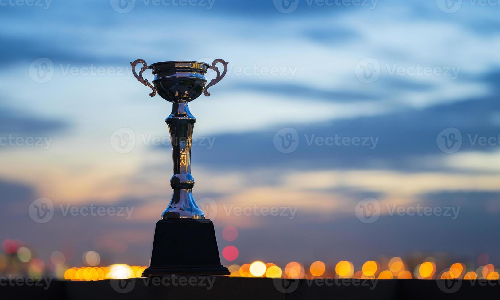 uma taça de troféu contra o fundo do céu nublado do crepúsculo foto