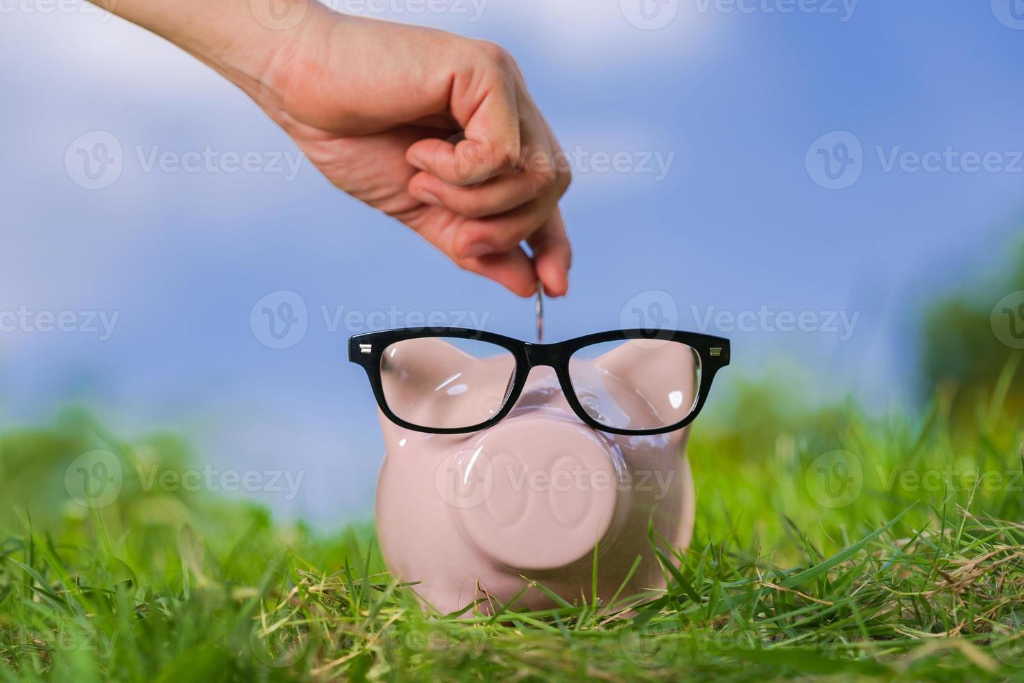 cofrinho rosa com óculos na grama e mão colocando uma moeda foto