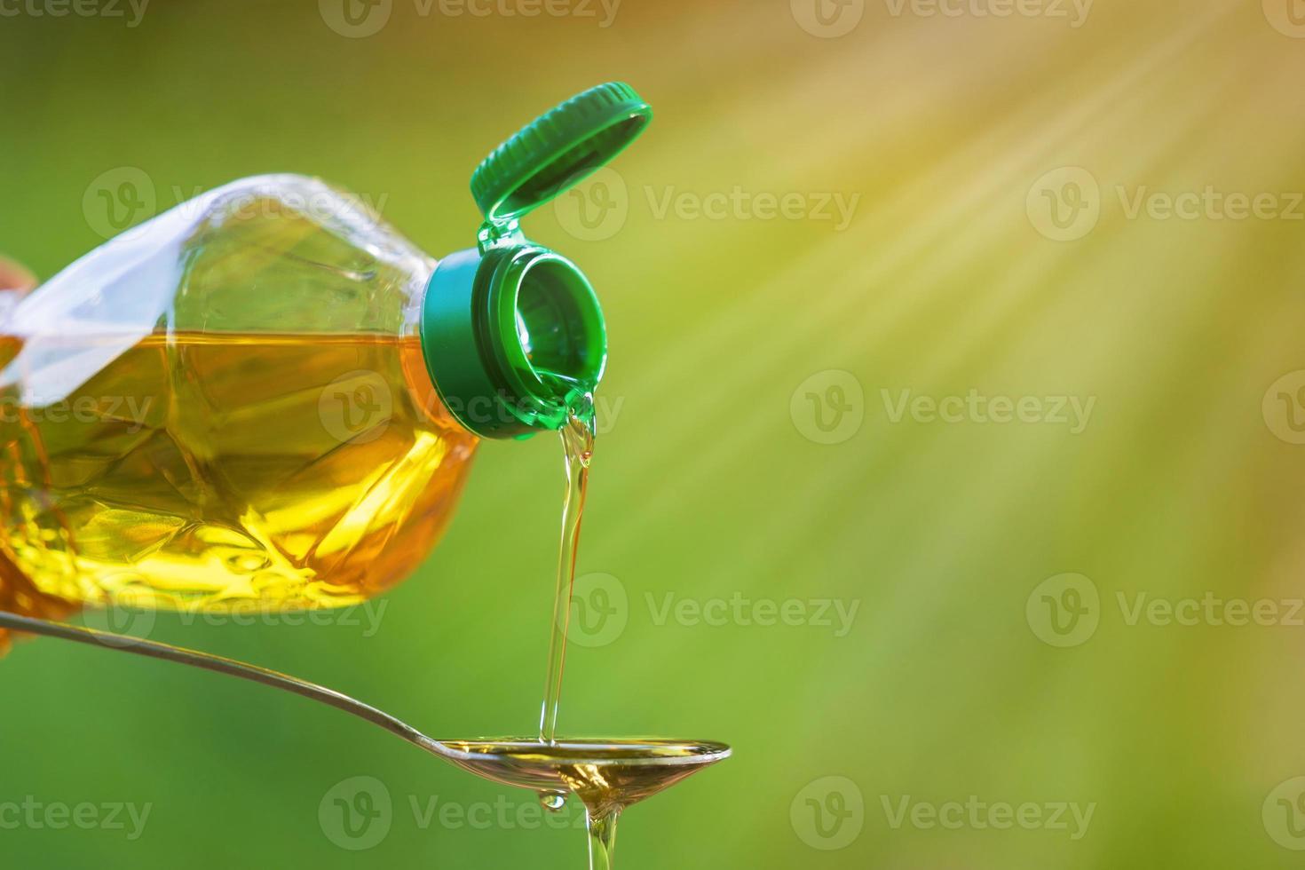 mão derramando óleo vegetal da garrafa para a colher foto