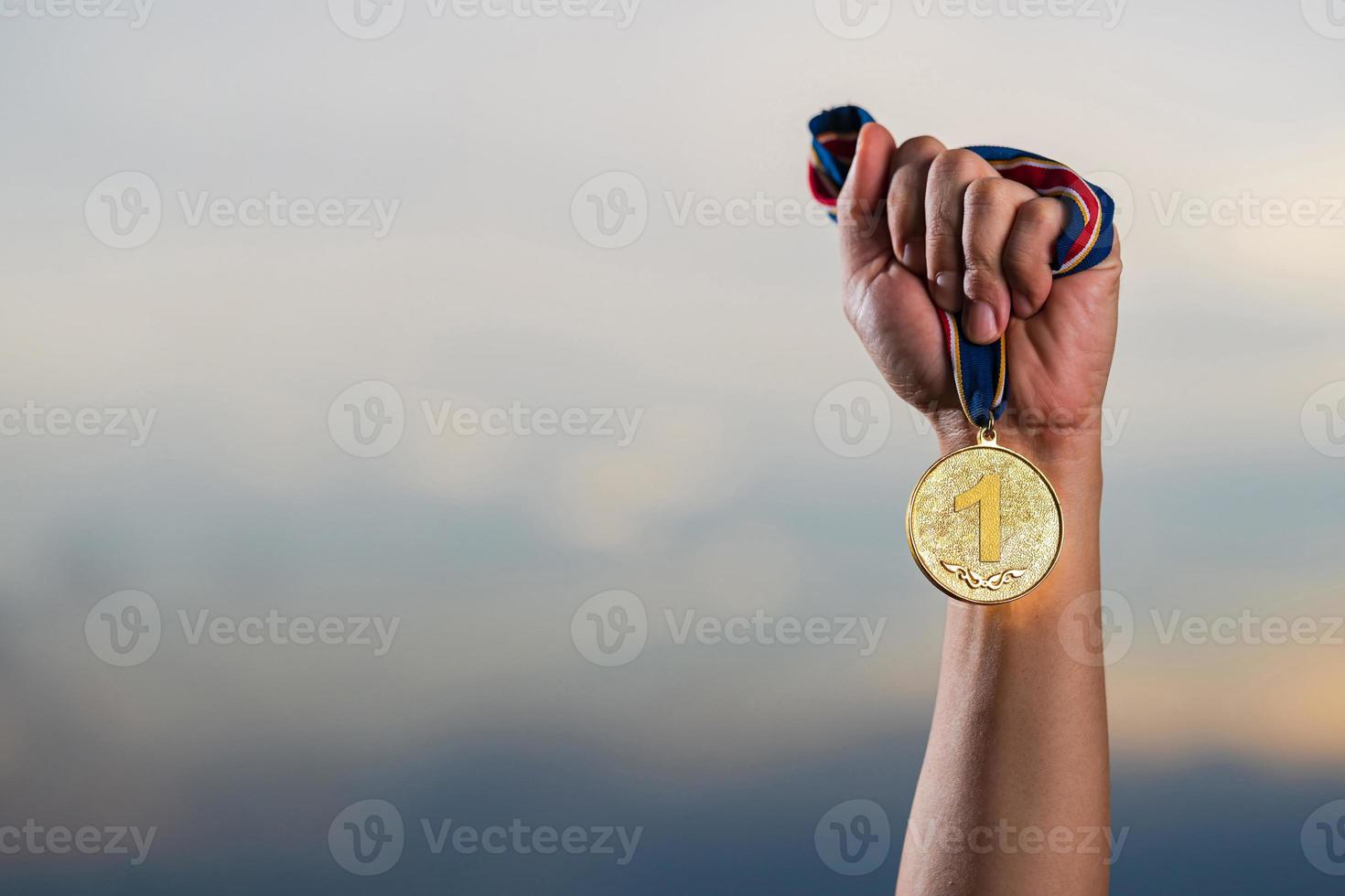 mão segurando a medalha de ouro contra o fundo do céu nublado do crepúsculo foto