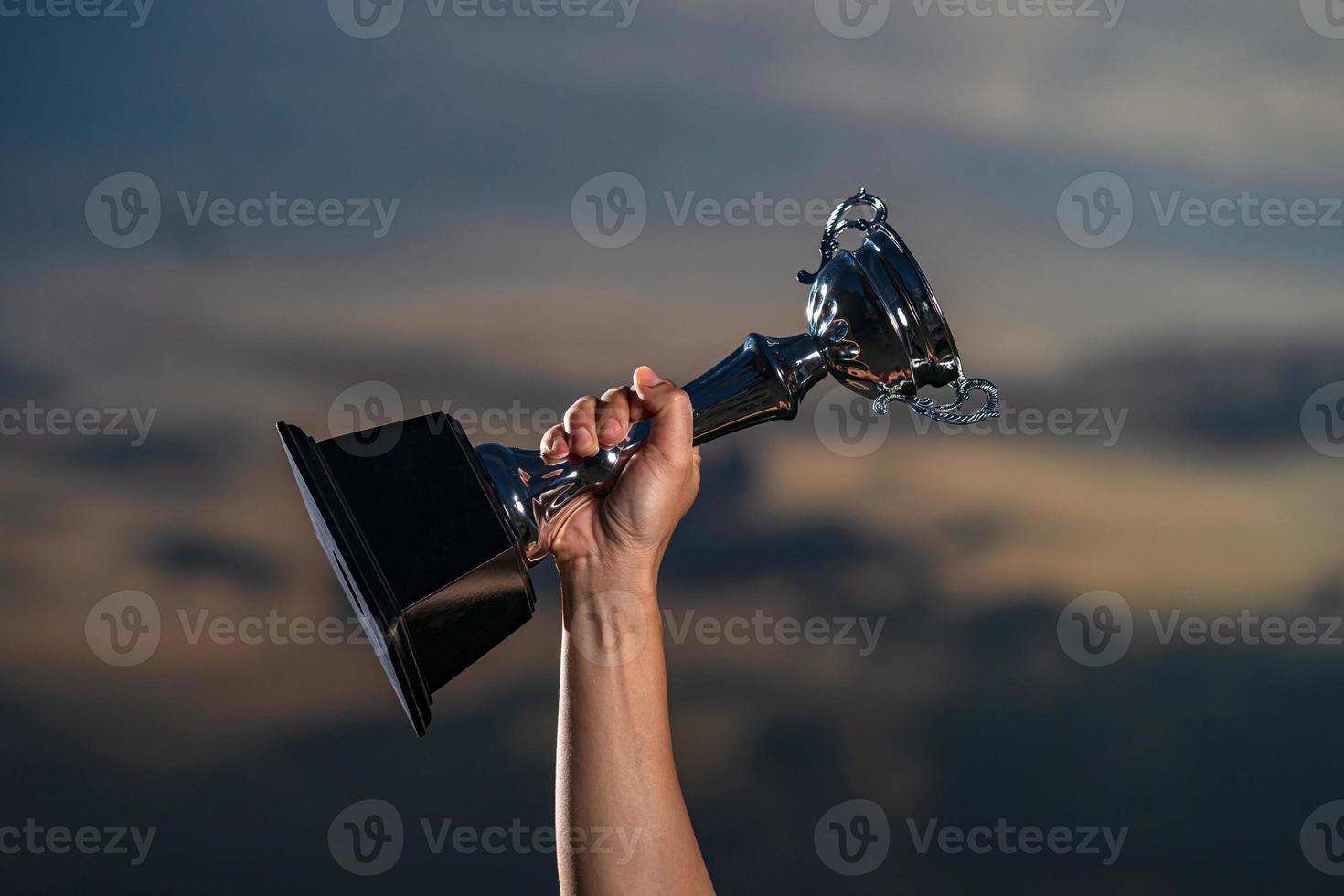 um homem segurando uma taça de troféu contra o fundo do céu nublado do crepúsculo foto