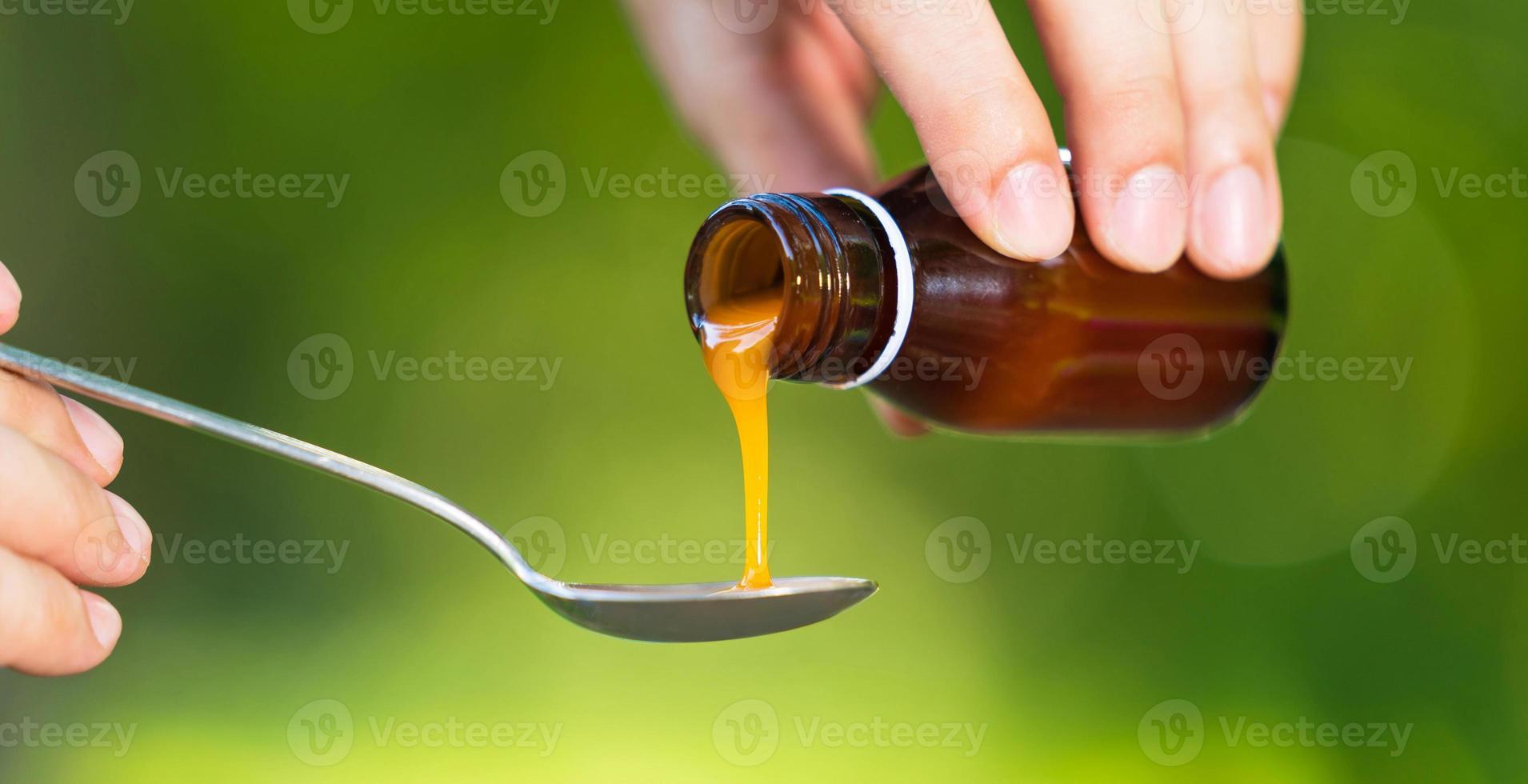mão do homem derramando medicação ou xarope antipirético da garrafa à colher foto