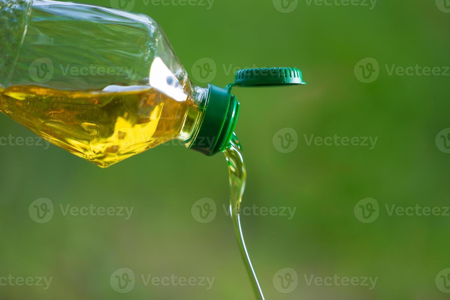 óleo vegetal derramando da garrafa com fundo natural foto