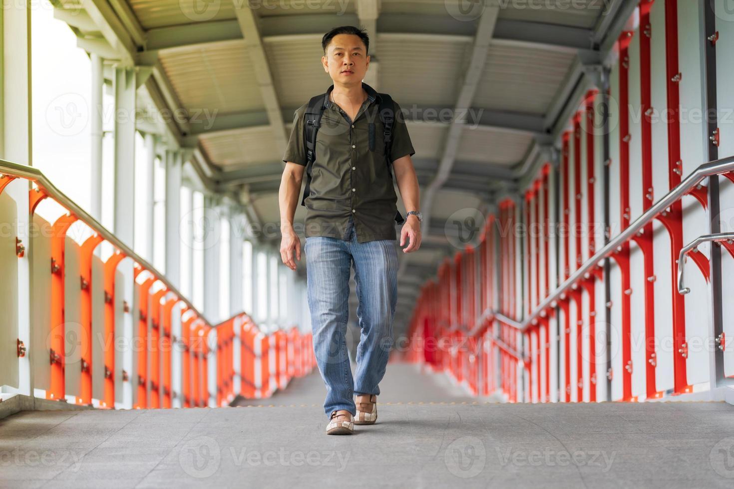 homem asiático caminhando na cidade foto