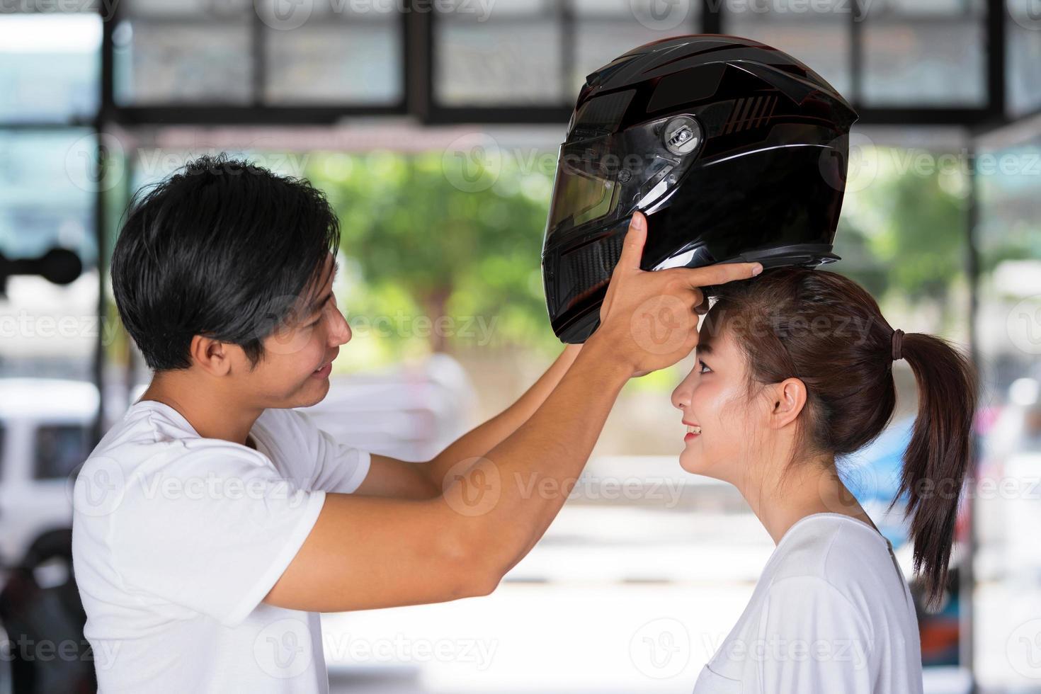 casal viajando em pé usando um capacete de motociclista foto