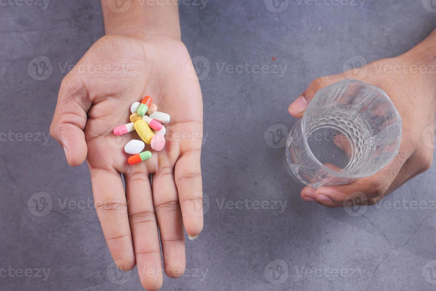 mão segurando comprimidos e um copo d'água foto