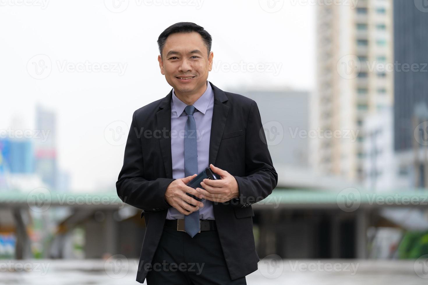 empresário asiático em pé e segurando um telefone celular com prédios de escritórios comerciais ao fundo da cidade foto