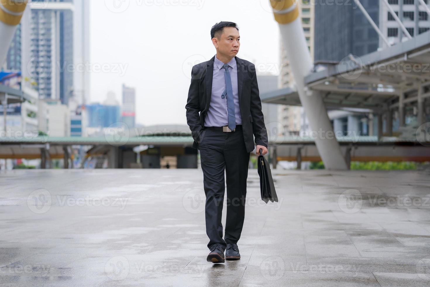 empresário asiático andando e segurando uma pasta com prédios de escritórios comerciais ao fundo da cidade foto