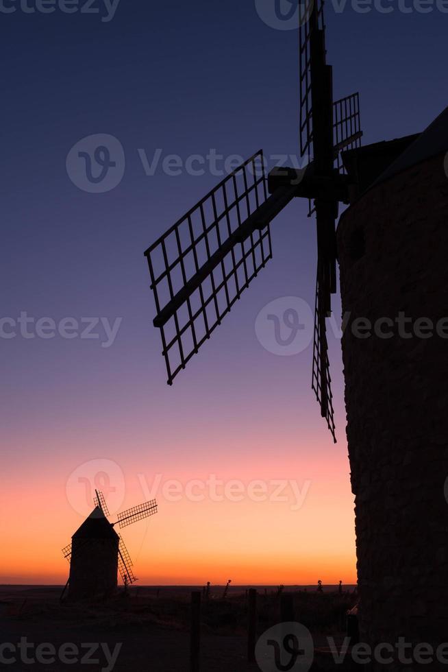 velhos moinhos de vento ao pôr do sol foto