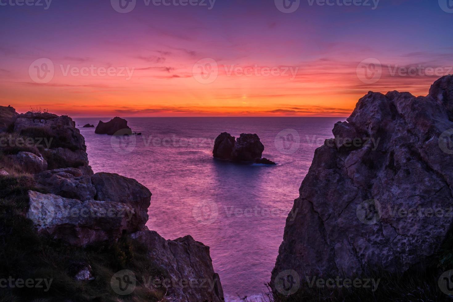 pôr do sol na praia rochosa foto