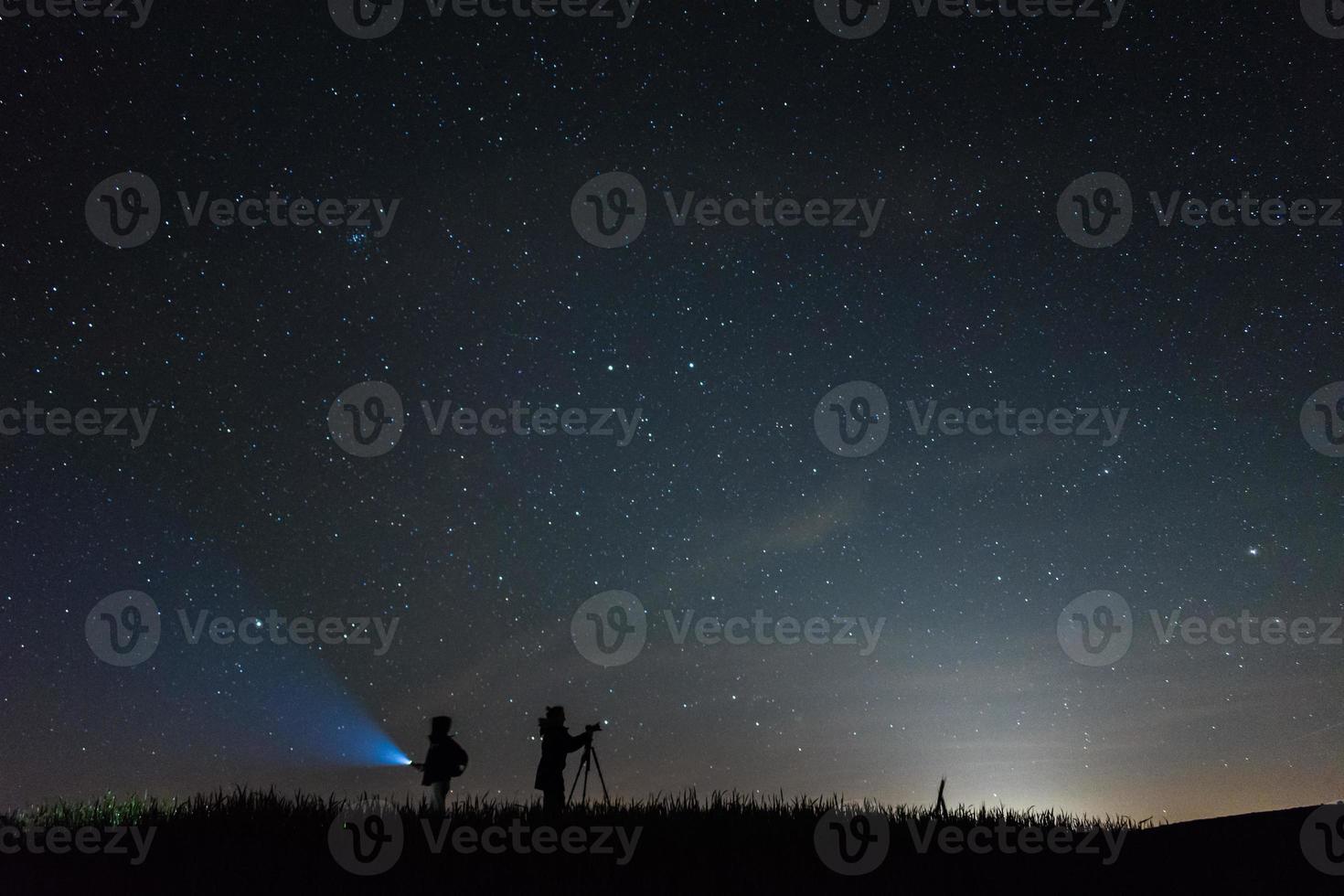 fotógrafos de silhueta com um fundo de céu cheio de estrelas à noite foto