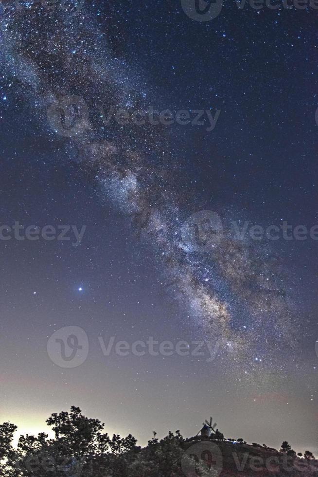a Via Láctea com um moinho de vento ao fundo foto