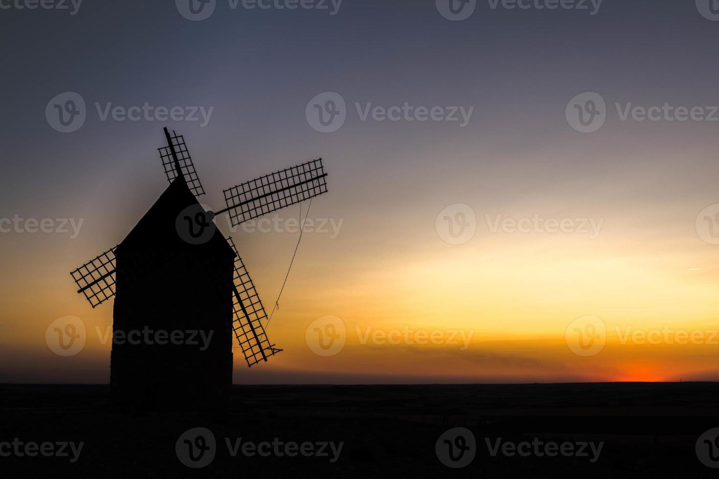 velho moinho de vento ao pôr do sol foto