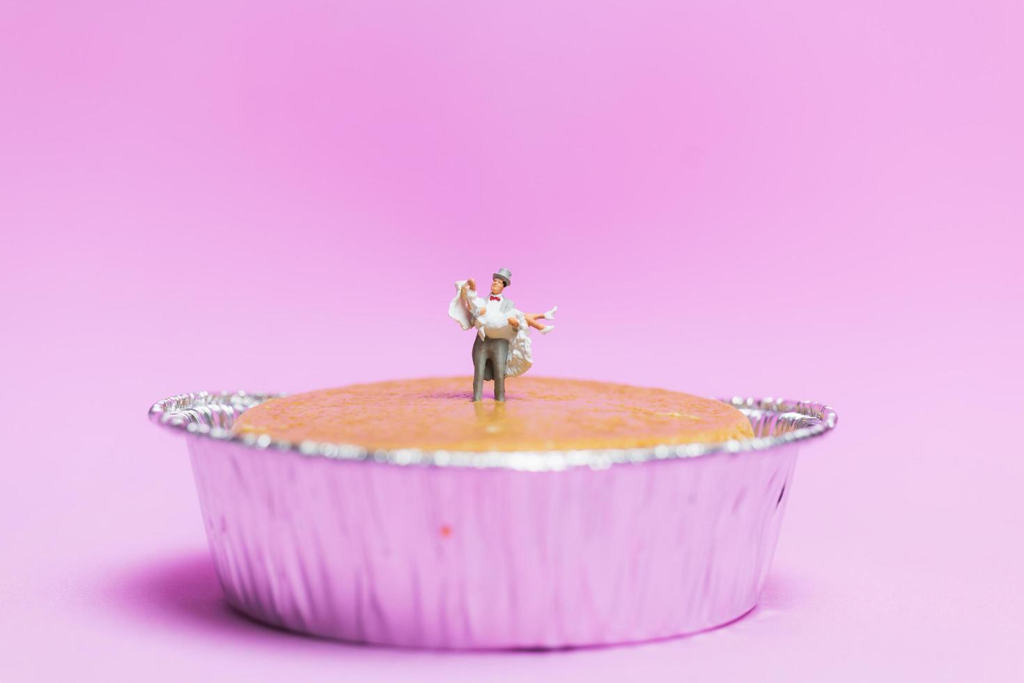 casamento em miniatura de um casal de noivos em um fundo rosa, conceito de dia dos namorados foto