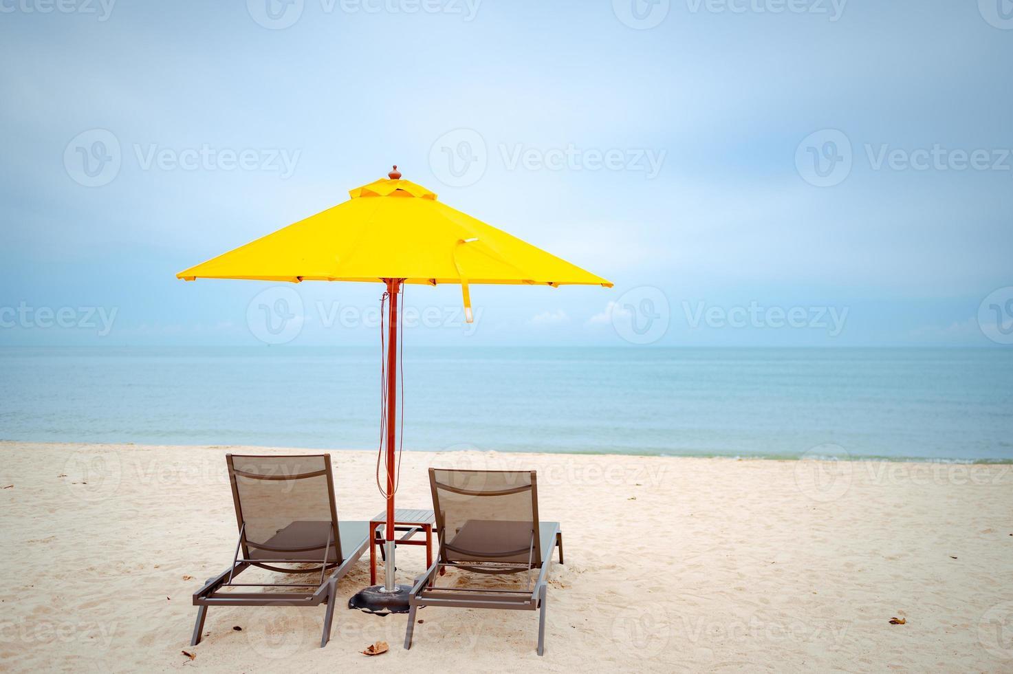 cadeiras de praia sob um guarda-sol amarelo na praia foto