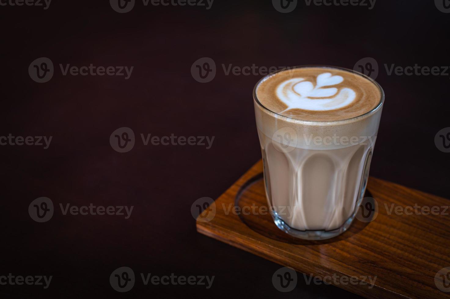 um copo de latte art em uma placa de madeira com fundo escuro foto