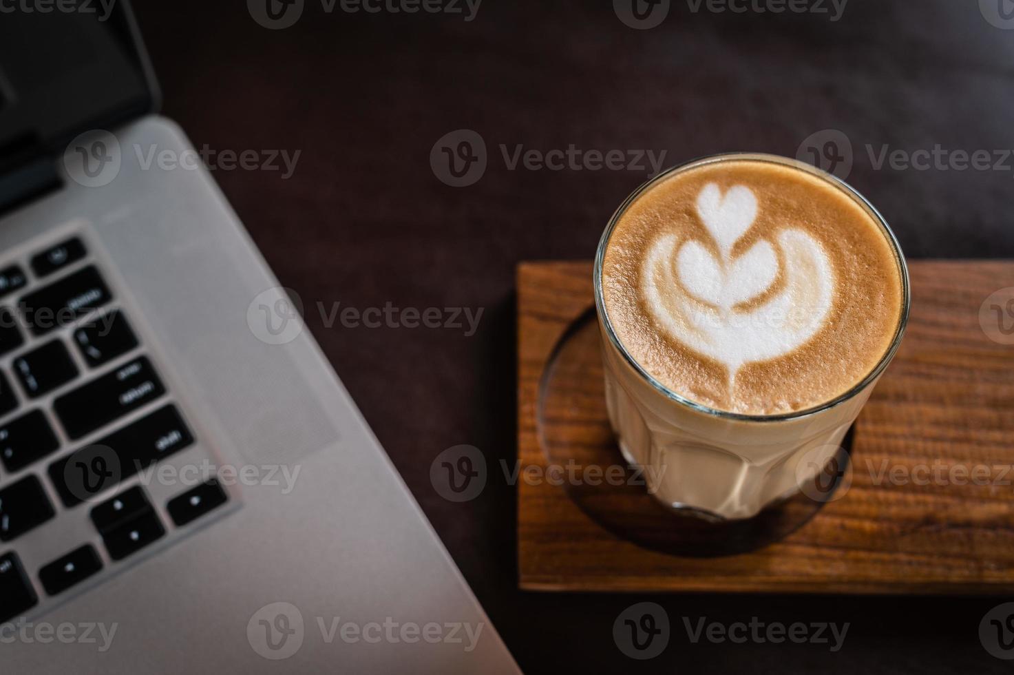 café com leite em um copo sobre uma mesa de madeira foto