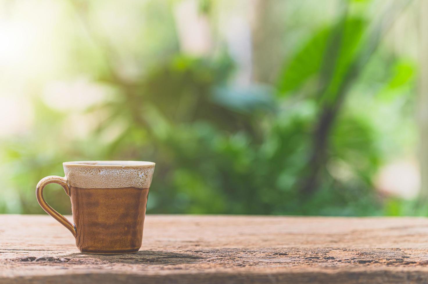 caneca de café na mesa com luz do sol foto