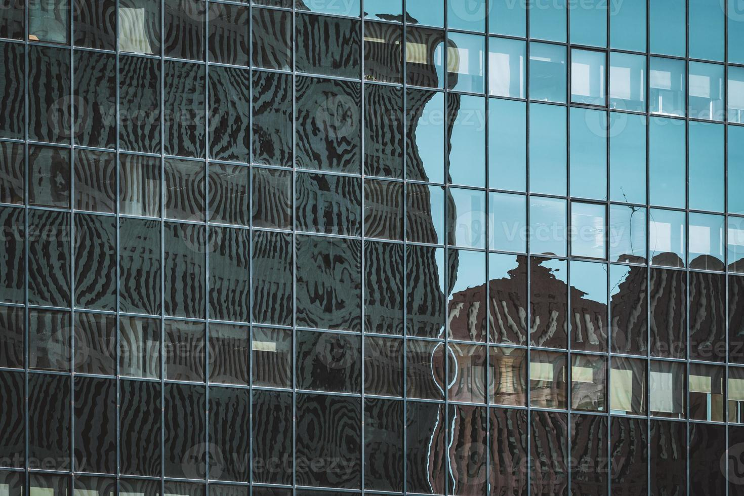 reflexos na fachada envidraçada de um prédio de escritórios foto
