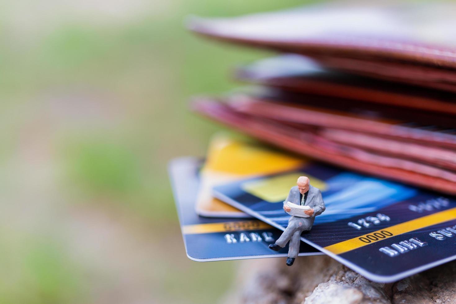 empresários em miniatura sentados sobre conceitos de cartão de crédito, negócios e finanças foto