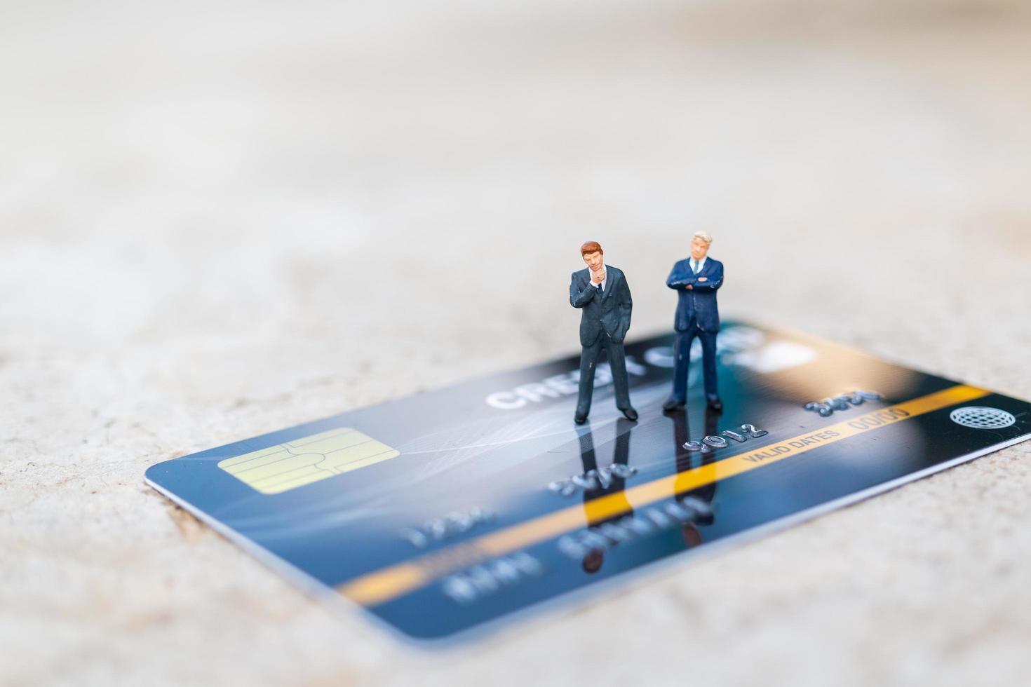 empresários em miniatura com conceitos de cartão de crédito, negócios e finanças foto