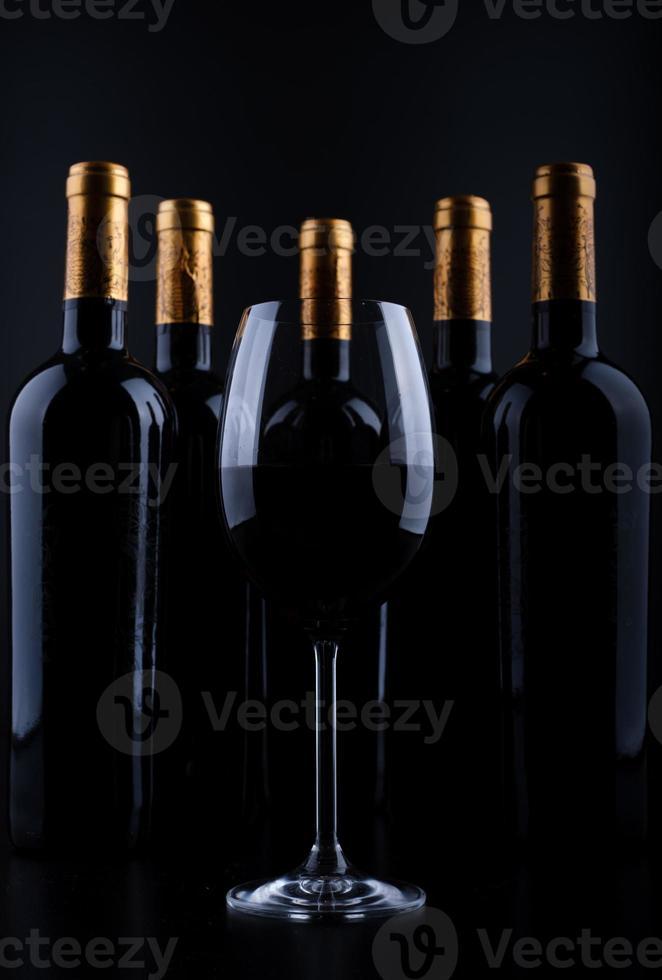 garrafas de vinho e copo com fundo preto foto
