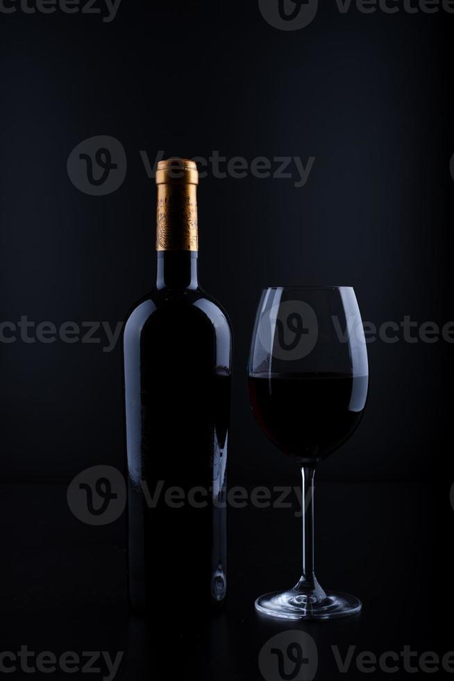 closeup garrafa de vinho e vidro com fundo preto foto