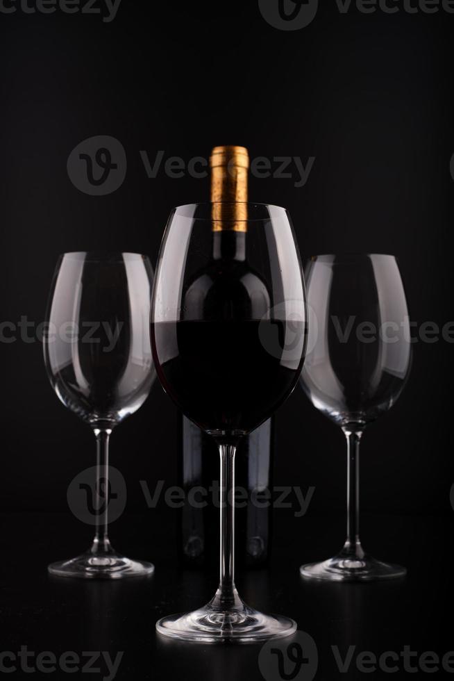 garrafas de vinho e copo cheio com fundo preto foto