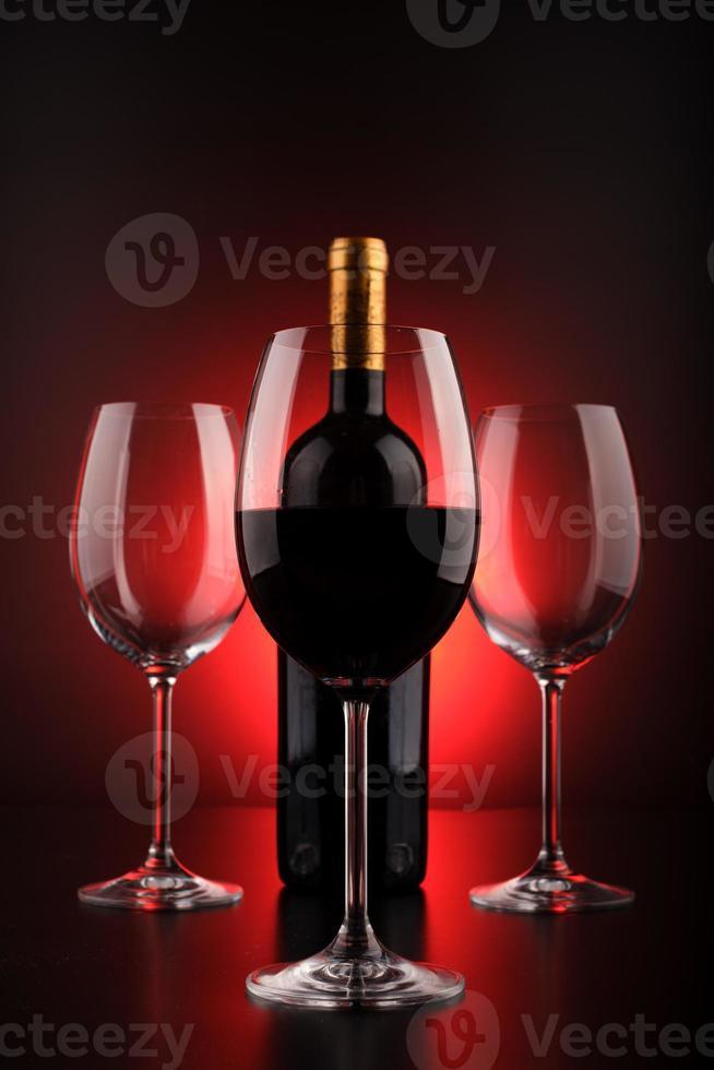 garrafas de vinho e copo cheio com fundo vermelho e preto foto