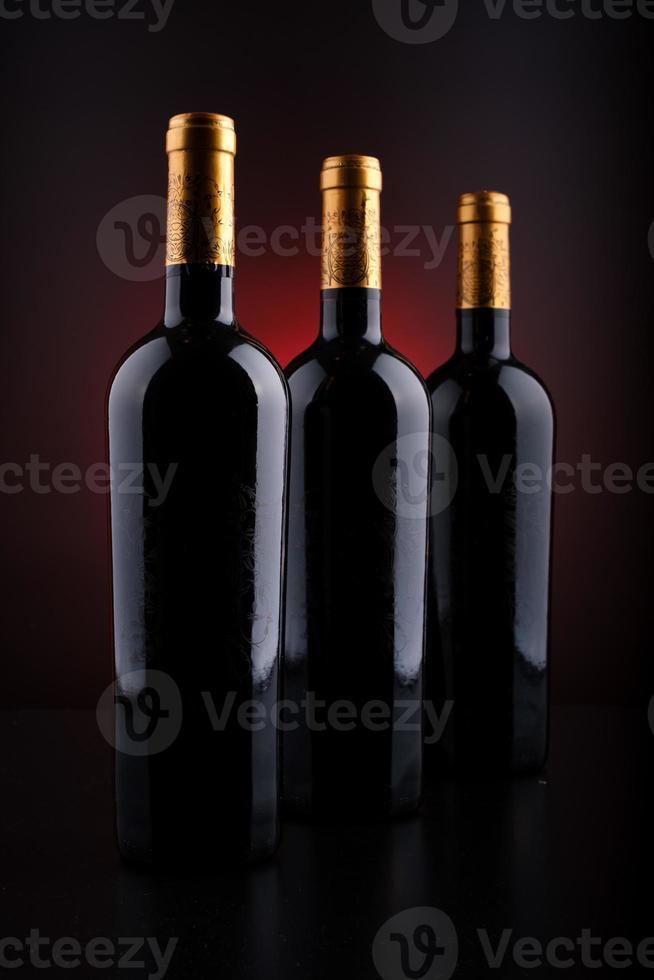 garrafas de vinho com fundo preto e vermelho foto