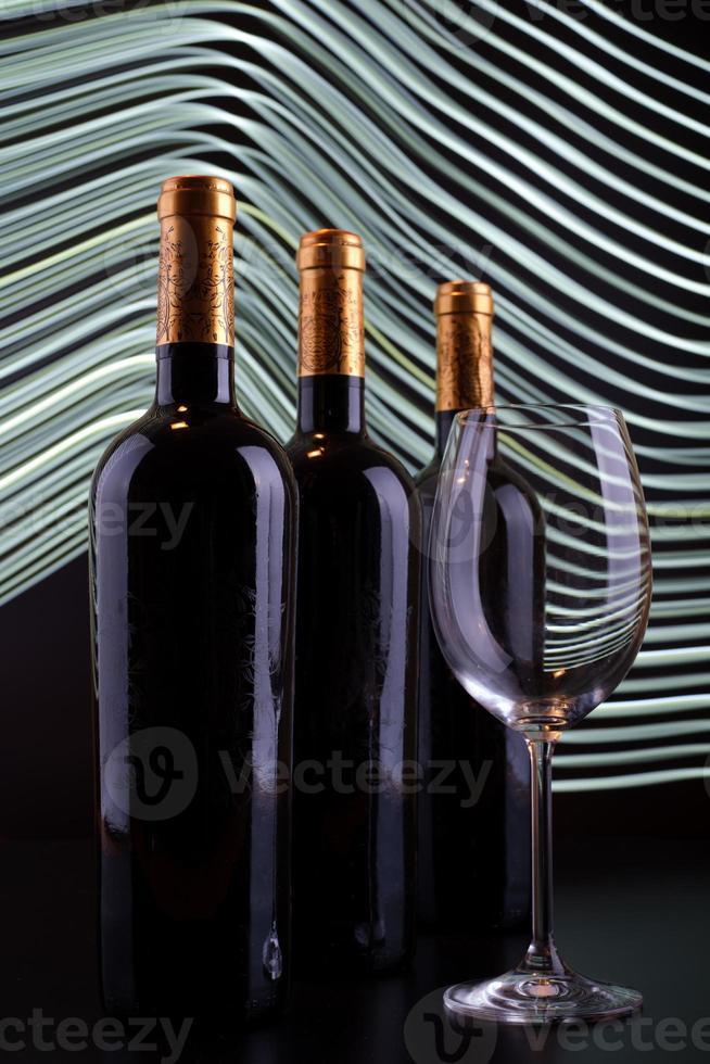 garrafas de vinho e copo com fundo de linhas brancas foto
