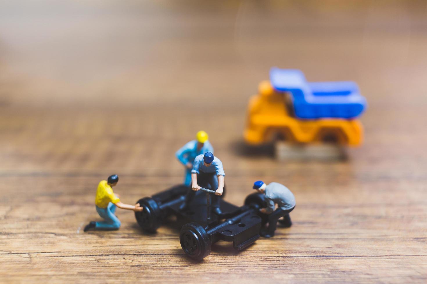 trabalhadores em miniatura consertando uma roda de um caminhão em um fundo de madeira foto