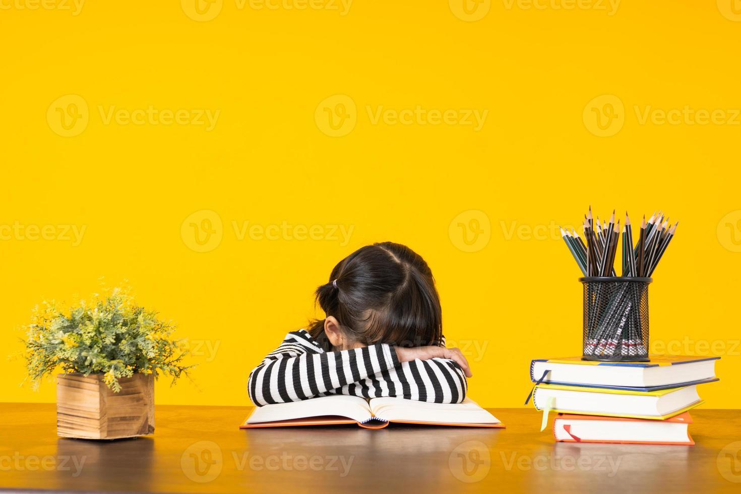 menina com escondeu nos braços cruzados sobre o livro aberto em uma mesa de madeira com outros livros e lápis com fundo amarelo foto